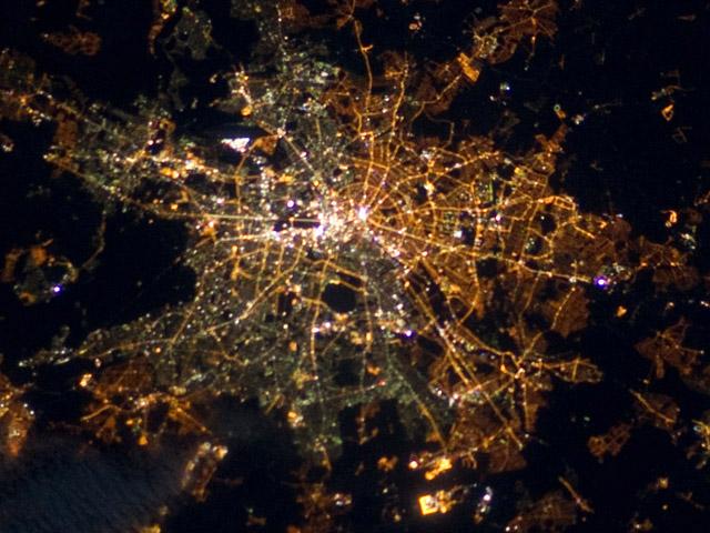 Berlin – geteilt leuchtende Stadt, aufgenommen am 5. April 2012 von der ISS. Die Laternen im Osten der Stadt leuchten gelblich, die Straßenbeleuchtung im Westen ist grünlich. Quelle: NASA (public domain).